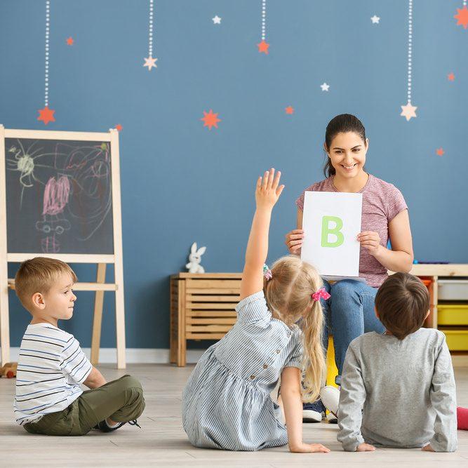 Cute little children learning letters in kindergarten