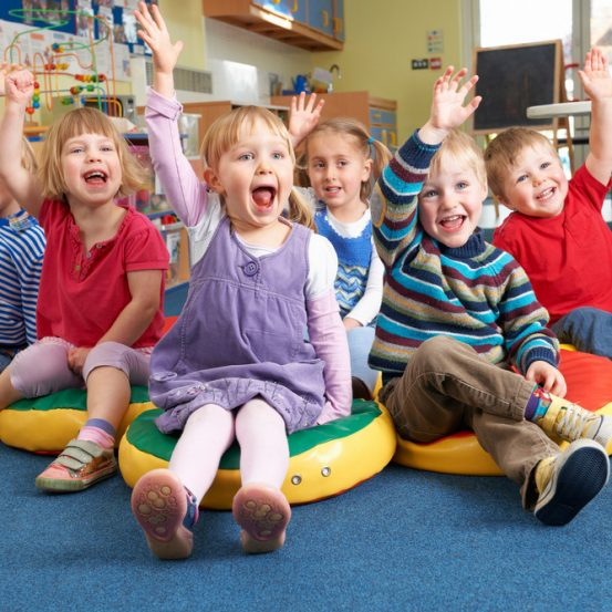 Group Of Pre School Children Answering Question In Classroom